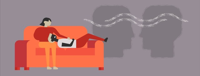 Husband suffering from migraine laying on couch with head in wife's lap.