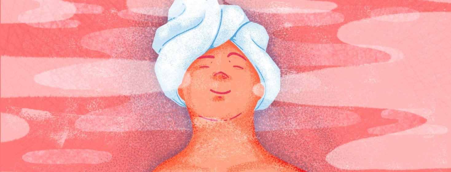 Woman relaxing with a towel on her head, eyes closed, and a smile on her face in a steam filled room.