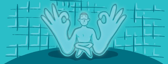 Figure in a meditative pose in a blue phototherapy chamber.