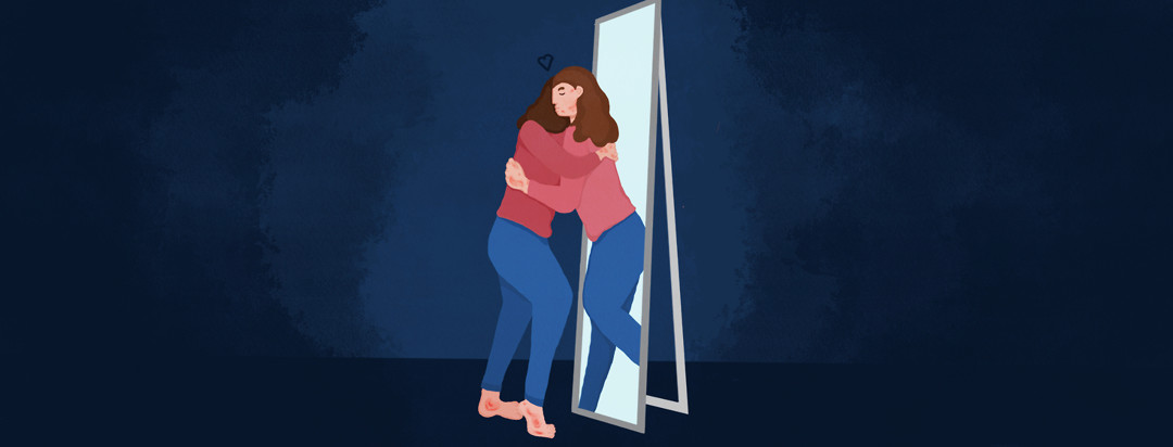 The reflection of a person with psoriasis giving herself a hug