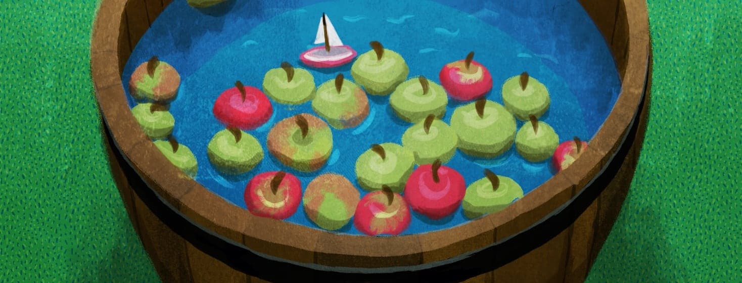 A barrel of water with apples floating on top. There is also a floating sail boat.