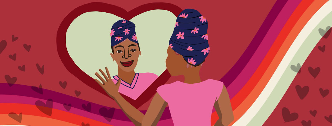 a Black woman wearing a head wrap smiles at herself in a heart shaped mirror